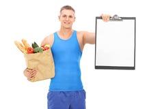 Junger Athlet, der Einkaufstüte und ein Klemmbrett hält Lizenzfreie Stockbilder