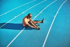 Junger Athlet, der herauf seine Schuhe vor einem Lauf bindet lizenzfreies stockbild