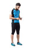 Junger Athlet in Radfahrentrikot und Gamaschen, die Handy halten und betrachten Lizenzfreies Stockfoto