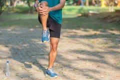 Junger Athletenmann, der in den Park im Freien ausdehnt m?nnlicher L?ufer w?rmen bereites zu auf der Stra?e drau?en r?tteln auf a stockfotografie