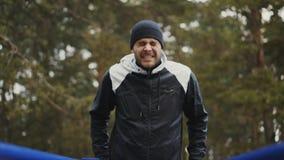 Junger Athletenmann, der draußen StoßUPS-Übung auf Stangen im Winterpark tut stock footage