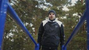 Junger Athletenmann, der draußen StoßUPS-Übung auf Stangen im Winterpark tut stock video