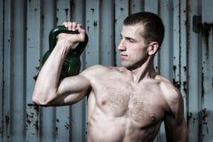 Junger Athletenmann, der Training mit schweren Gewichten auf dem Hintergrund einer grauen Metallwand tut Stockbild