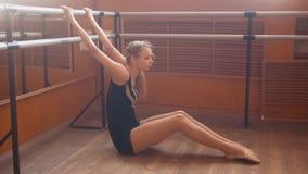 Junger athletischer Frauenturner, der Bein auf Barre in einem Studio ausdehnend tut Lizenzfreie Stockfotos