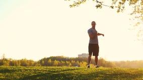 Junger athletischer Läufer, der die Übung, bereitend für Training im Park ausdehnend tut vor Sonnenuntergang, getontes Video stock video