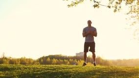 Junger athletischer Läufer, der die Übung, bereitend für Training im Park ausdehnend tut vor Sonnenuntergang, getontes Video stock footage