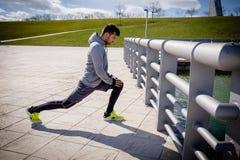 Junger athletischer Mann bereitet vor sich, bevor er läuft lizenzfreie stockbilder