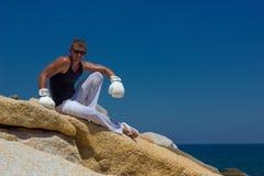Junger athletischer Mann in den Boxhandschuhen auf dem Meer Marineart Stockfoto
