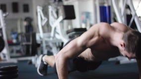 Junger athletischer Mann, den das Handeln drückt, ups in eine Turnhalle mit dem nackten Torso stock video