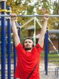 Junger athletischer Mann, der draußen Sportübungen im Park tut stockfoto