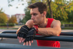 Junger athletischer Mann, der eine Pause während des Ausarbeitens im Freien macht Lizenzfreie Stockbilder