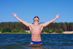 Junger athletischer Mann, der im Wasser aufwirft Lizenzfreie Stockfotografie