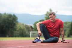 Junger athletischer Mann, der vor laufender Übung ausdehnt lizenzfreie stockfotografie