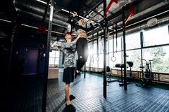 Junger athletischer Mann hilft schlankem hübschem Mädchen zu tun hochziehen auf der Stange in der Turnhalle lizenzfreie stockfotografie