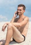 Junger athletischer Mann mit Mobiltelefon auf dem Strand Stockbild