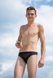 Junger athletischer Mann mit Mobiltelefon auf dem Strand Lizenzfreie Stockbilder