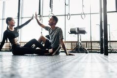 Junger athletischer Mann und dünnes Mädchen sitzen auf dem Boden und geben fünf in der Turnhalle lizenzfreie stockfotos