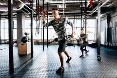 Junger athletischer Mann und dünnes Mädchen tun Sportübungen mit spezieller Ausrüstung wie Machtband in der Turnhalle lizenzfreie stockfotos