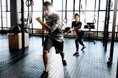Junger athletischer Mann und dünnes Mädchen tun Sportübungen mit spezieller Ausrüstung wie Machtband in der Turnhalle stockfotografie