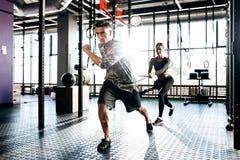 Junger athletischer Mann und dünnes Mädchen tun Sportübungen mit spezieller Ausrüstung wie Machtband in der Turnhalle stockfoto