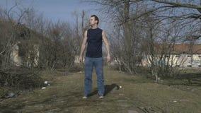 Junger attraktiver Athlet, der in einem verlassenen Platz stillsteht stock footage