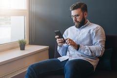 Junger attraktiver bärtiger Geschäftsmann im Hemd und in den Gläsern sitzt auf Sofa im Raum und benutzt Smartphone Hippie-Mannfun Lizenzfreie Stockbilder