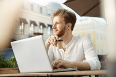 Junger attraktiver bärtiger Ingwerkerl mit Ohrring im weißen Hemd trinkt den Kaffee und entfernt arbeitet an neuem Projekt auf se lizenzfreie stockfotografie