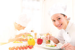 Junger attraktiver Berufschef, der in seiner Küche kocht stockfoto