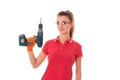 Junger attraktiver Brunettefrauenerbauer in der Uniform mit Gläsern und bohren herein ihre Hände machen reovations lokalisiert au stockfoto