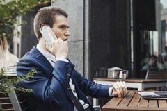 Junger attraktiver Brunettegeschäftsmann, der durch Handy im Café spricht stockfotografie
