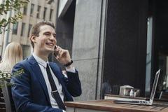 Junger attraktiver Brunettegeschäftsmann, der durch Handy und das Lächeln spricht lizenzfreie stockfotos