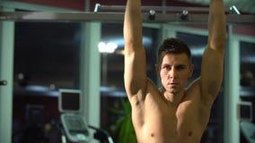 Junger attraktiver erwachsener Mann in einer Eignungsturnhalle Er steht zwischen Übungen und dem Betrachten der Seite still Sport stock video