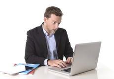 Junger attraktiver europäischer Geschäftsmann, der im Druck am Schreibtischcomputer schaut Monitor im Schock arbeitet Stockfotografie