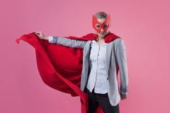 Junger attraktiver Frauensuperheld Mädchen in einem Anzug und eine Maske mit rotem Mantel des Helden stockbild
