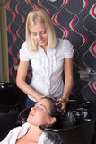 Junger attraktiver Friseur wäscht den Mädchenkopf im Friseursalon Stockbilder