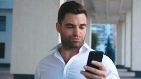 Junger attraktiver Geschäftsmann Using Smartphone nahe Bürogebäude Schauen erfolgreich Bärtiges Tragen des gut aussehenden Mannes stock video footage