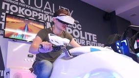 Junger attraktiver hübscher Kerl reitet ein Motorrad in der virtuellen Realität Feiertage, Innovation, Schirm, Neon, Fahrrad, küh stock video