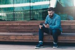 Junger attraktiver Hippie-Mann sitzt auf, trinkendem Kaffee der Holzbank im Freien und hört Musik auf seinem Smartphone Stockfoto