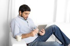 Junger attraktiver hispanischer Mann zu Hause auf weißer Couch unter Verwendung der digitalen Tablette oder der Auflage Stockfotos