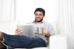 Junger attraktiver hispanischer Mann zu Hause auf weißer Couch unter Verwendung der digitalen Tablette oder der Auflage Stockfotografie