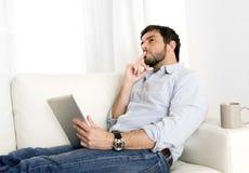 Junger attraktiver hispanischer Mann zu Hause auf weißer Couch unter Verwendung der digitalen Tablette oder der Auflage stockbild