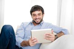 Junger attraktiver hispanischer Mann zu Hause auf weißer Couch unter Verwendung der digitalen Tablette oder der Auflage Lizenzfreie Stockbilder