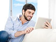 Junger attraktiver hispanischer Mann zu Hause, der auf weißer Couch unter Verwendung der digitalen Tablette sitzt Stockbild