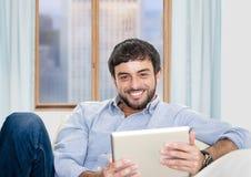 Junger attraktiver hispanischer Mann zu Hause, der auf weißer Couch unter Verwendung der digitalen Tablette sitzt lizenzfreie stockfotografie