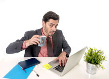 Junger attraktiver lateinischer Geschäftsmann im Anzug und Bindung, die am Bürocomputertischtrinkbecher Kaffee arbeitet Stockfoto