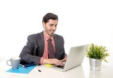 Junger attraktiver lateinischer Geschäftsmann im Anzug und Bindung, die am Schreibenc$schauen des Bürocomputertischs glücklich un Stockfotografie