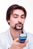 Junger attraktiver Mann betrachtet andeutend ein Rasierapparatversuchen Stockfotos