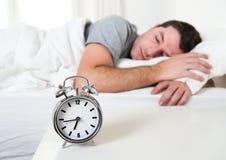 Junger attraktiver Mann, der auf Bett schläft Lizenzfreie Stockfotografie