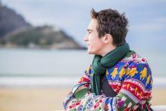 Junger attraktiver Mann, der auf dem Ufer und den Blicken in dem Meer steht Lizenzfreie Stockfotografie