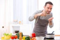 Junger attraktiver Mann, der in einer Küche kocht Lizenzfreie Stockfotografie